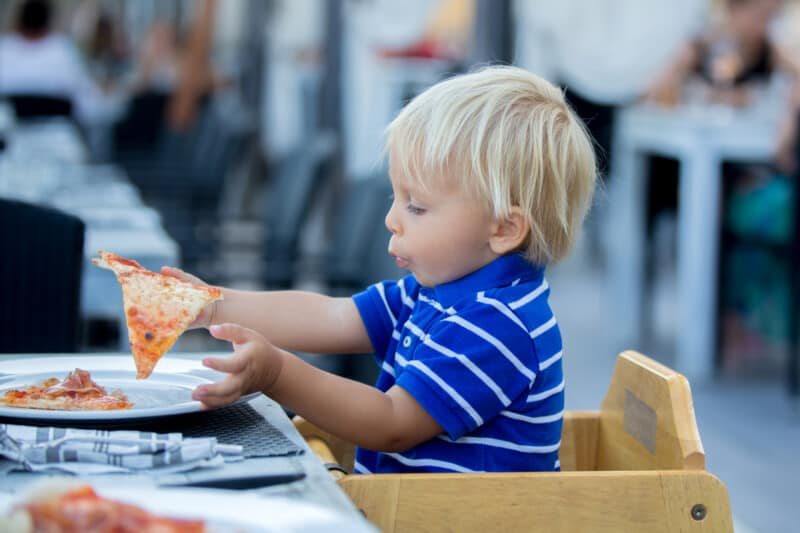 little boy eating slice of pizza at a restaurant where kids eat free