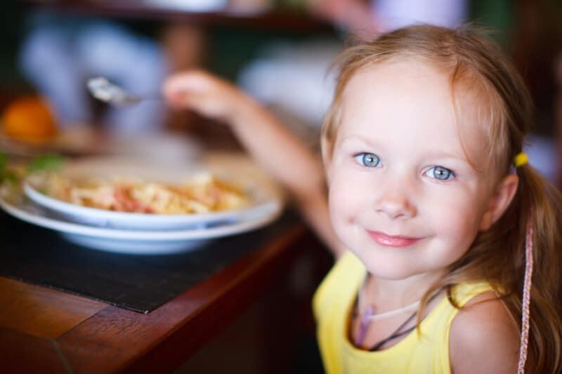 happy little girl eating dinner at a restaurant where kids eat free