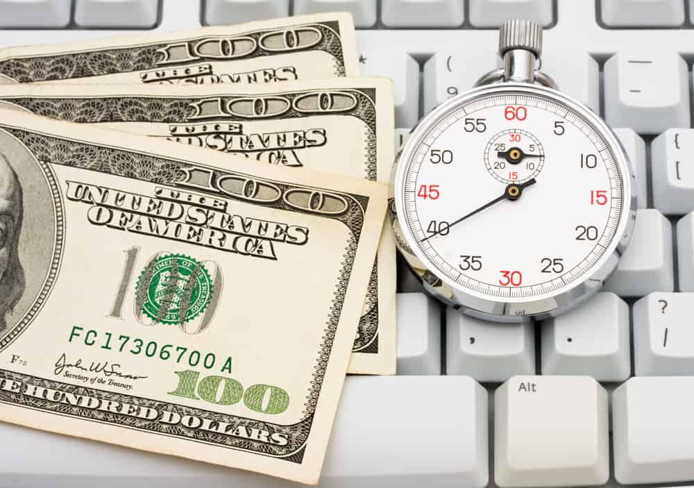 One hundred dollar bills sitting on a computer keyboard, making money online