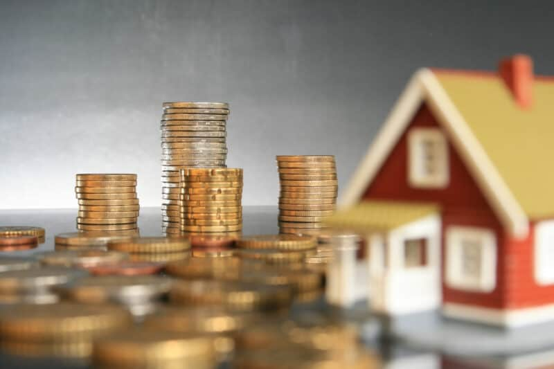 coin stacks and toy house showing real estate concept as one of the best ways to invest money