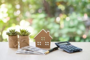 Home Loan, mortgage and real estate concept, House model with pile of dollar bills, calculator, pen and plant pots on table with garden background for business, finance, banking, and saving money.