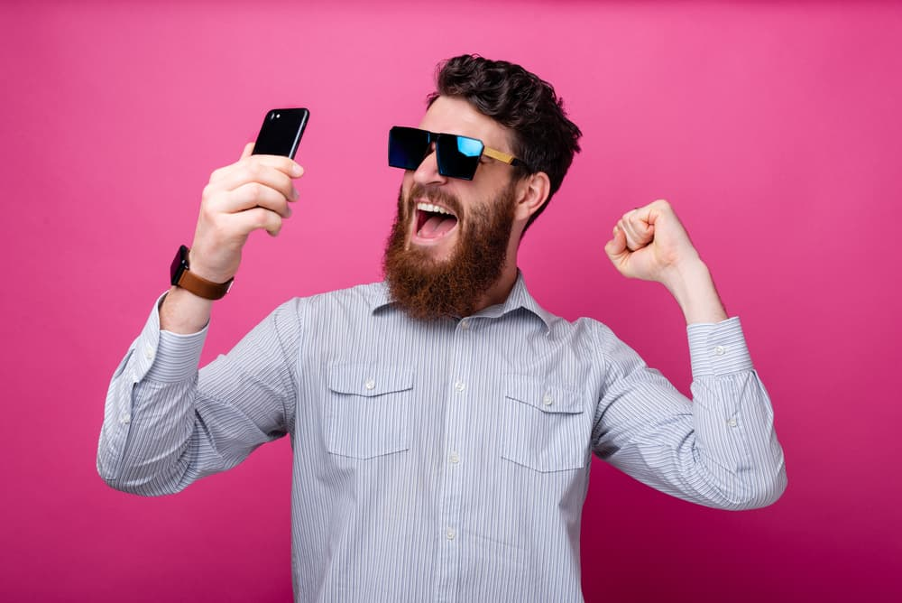 Portrait of amazed bearded man in casual holding smartphone and celebrating victory