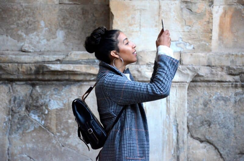 woman taking pictures on her smartphone on a vacation after saving money with cheap cell phone plans