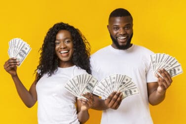 Cheerful Black Couple Holding Money, yellow studio background, panorama
