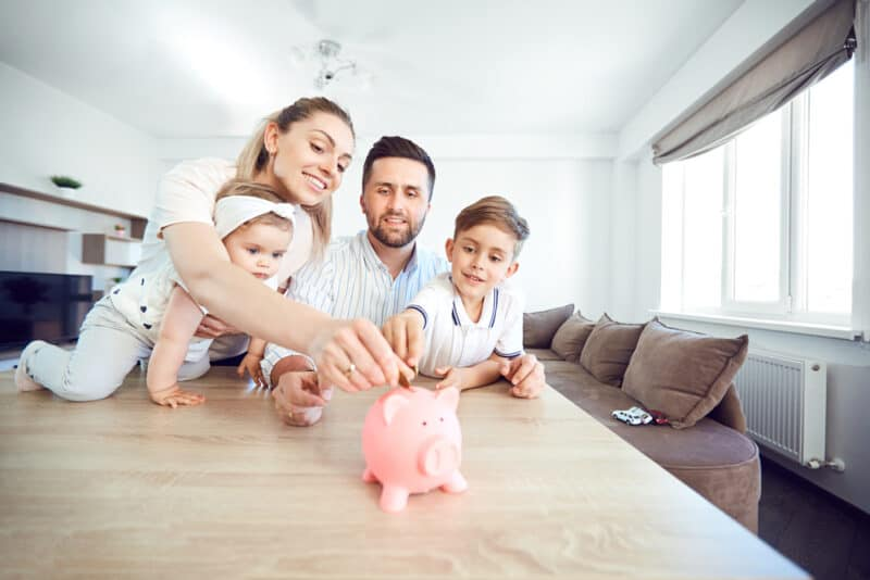 A smiling family saves money with a piggy bank. Happy family at the table in the room with a great money mindset.