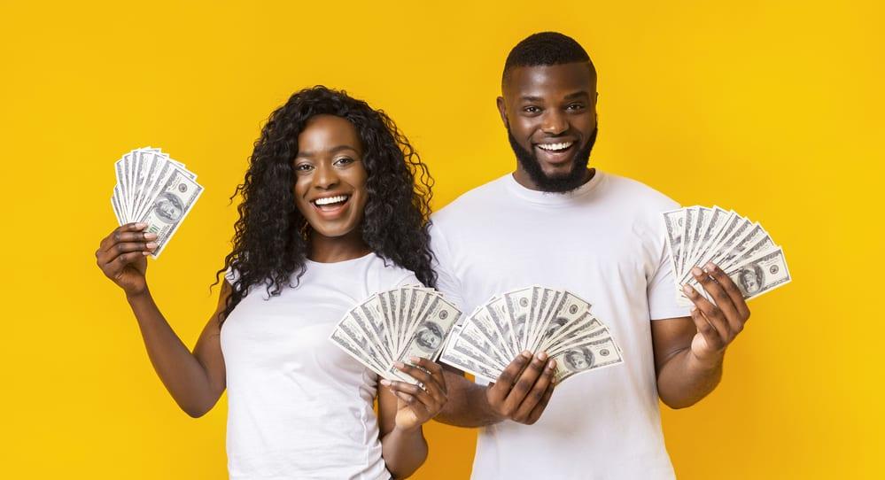 Cheerful Black Couple Holding Money, yellow studio background, panorama