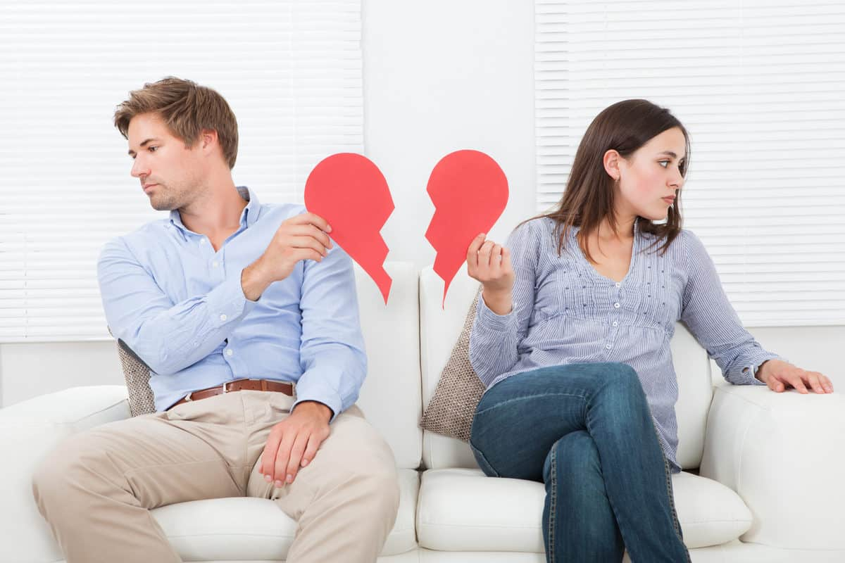 Full length of couple ignoring each other while sitting on sofa at home; reasons for divorce