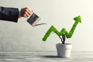 M1 Finance Review Hand of woman watering small plant in pot shaped like growing graph