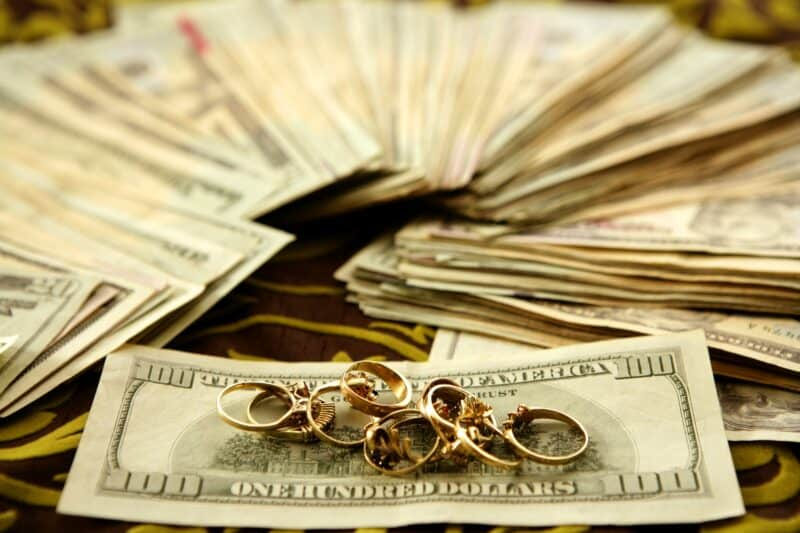 Dollar notes and gold rings over tablecloth, studio recreation
