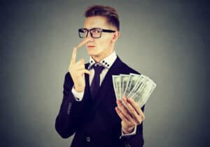 financial infidelity Financial fraud concept. Liar young business man in suit and glasses with dollar cash