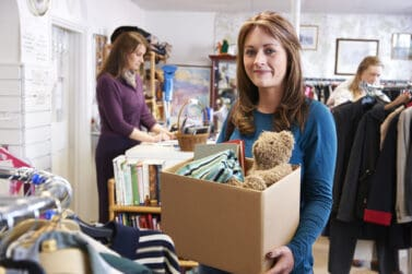 Online Flea markets Woman Donating Unwanted Items To Charity Shop