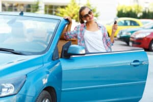 How to buy a used car Young pretty woman in sunglasses standing near convertible with keys in hand - concept of buying a used car or a rental car