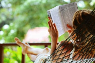 Get Paid To Read Books Young woman reading a book lying in a hammock