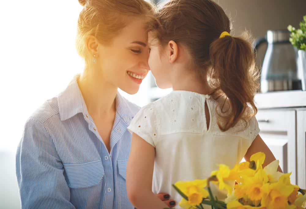 Gifts For Mom Who Doesn't Want Anything happy mother's day! child daughter congratulates mother and gives a bouquet of flowers to narcissus and gift