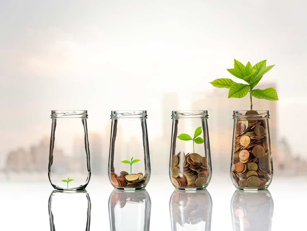 M1 Finance vs. Robinhood Gold coins and seed in clear bottle on cityscape photo blurred cityscape background,Business investment growth concept
