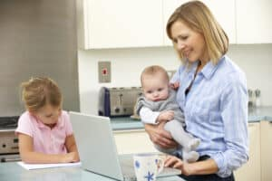side hustles for moms Mother with children using laptop in kitchen