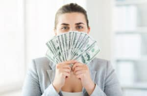 high paying jobs with no experience business, finance, saving, banking and people concept - close up of woman hiding her face behind us dollar money fan