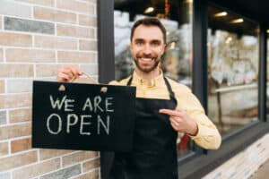 how to start a business with no moeny open sign Welcome, we are open. Portrait of caucasian attractive male waiter standing outdoors near a restaurant or cafe, points a finger at a signboard OPEN and friendly smile. Support small business concept