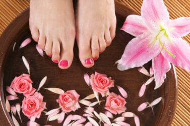 sell feet pics Spa background with a beautiful legs, flowers, petals and ceramic bowl